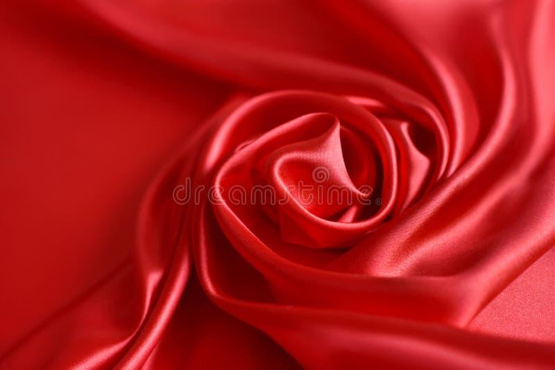 Sluit omhoog van rimpelingen in vorm van roze bloem op rode zijdestof Satijn textielachtergrond royalty-vrije stock fotografie