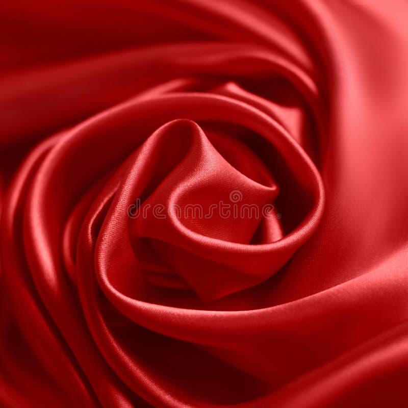 Sluit omhoog van rimpelingen in vorm van roze bloem op rode zijdestof Satijn textielachtergrond stock afbeelding