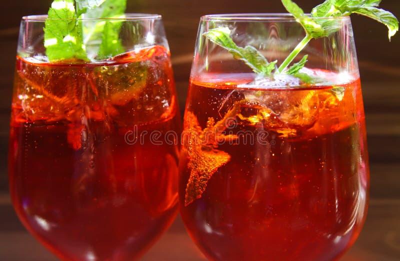Sluit omhoog van rode cocktail met bladeren van de ijsblokjes de groene munt in wijnglas royalty-vrije stock afbeeldingen
