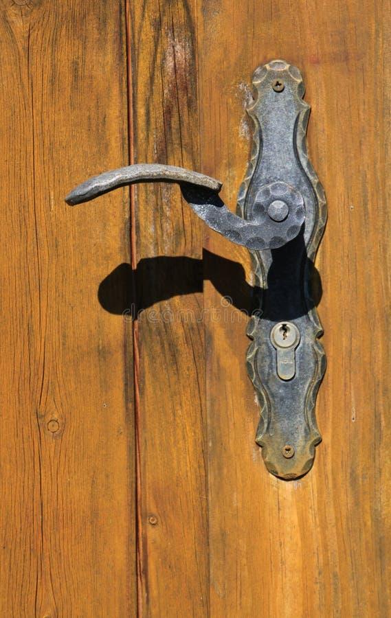 Sluit omhoog van roestig metaalhandvat bij oude bruine houten deur in helder zonlicht royalty-vrije stock foto's