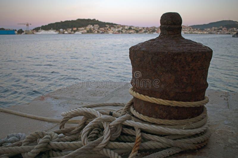 Sluit omhoog van roestige bootmeertros met rond verpakte kabels stock fotografie