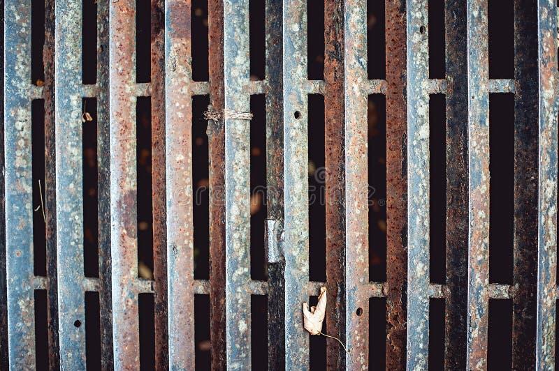 Sluit omhoog van roestige ijzerrooster op de weg stock foto