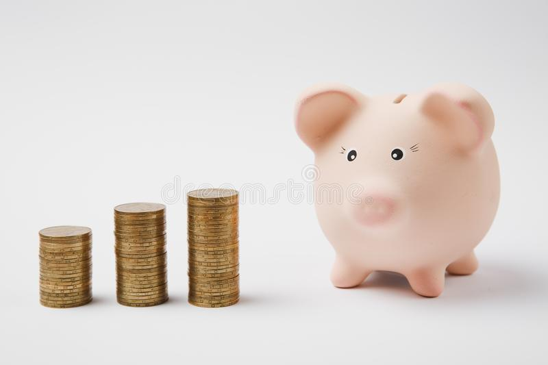 Sluit omhoog van roze piggy geldbank, stapels gouden muntstukken die op witte muurachtergrond worden geïsoleerd Geldaccumulatie royalty-vrije stock afbeelding
