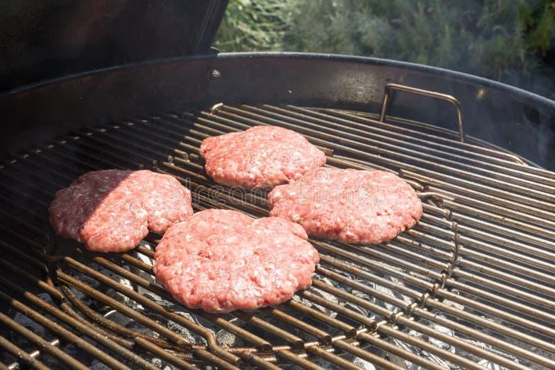 Sluit omhoog van Rundvleeshamburger het Koken op een Houtskoolgrill stock afbeelding