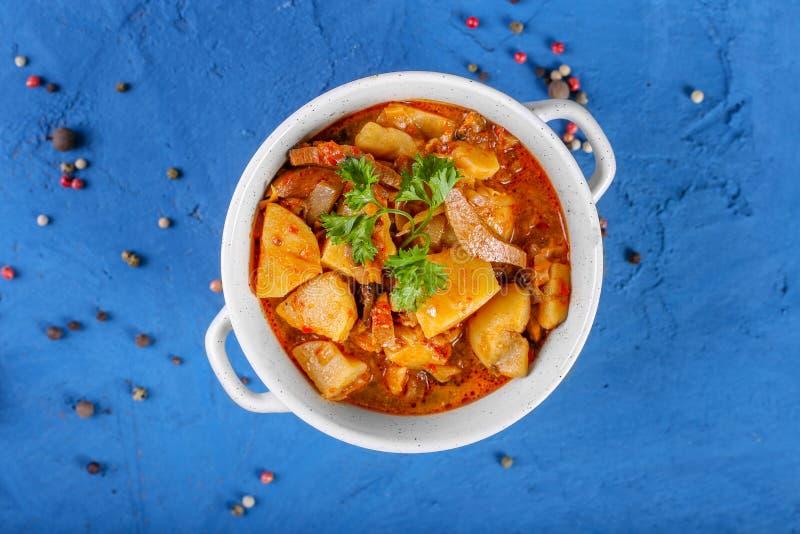 Sluit omhoog van saltwort met vlees, aardappels, tomatensaus en paddestoelen in een kom op een steen blauwe achtergrond Hoogste m stock foto