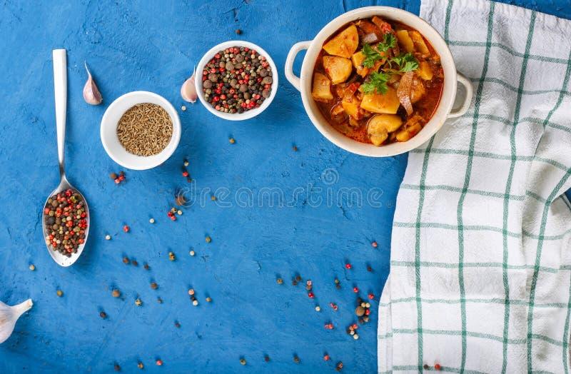 Sluit omhoog van saltwort met vlees, aardappels, tomatensaus en paddestoelen in een kom op een steen blauwe achtergrond Hoogste m stock afbeelding