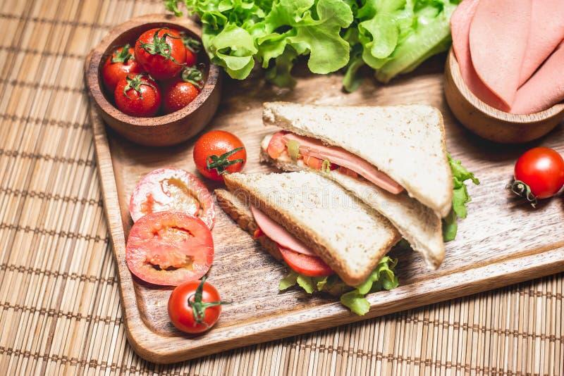 Sluit omhoog van sandwiches en ham met tomaten, Dubbeldekker met kaas en groente royalty-vrije stock afbeelding