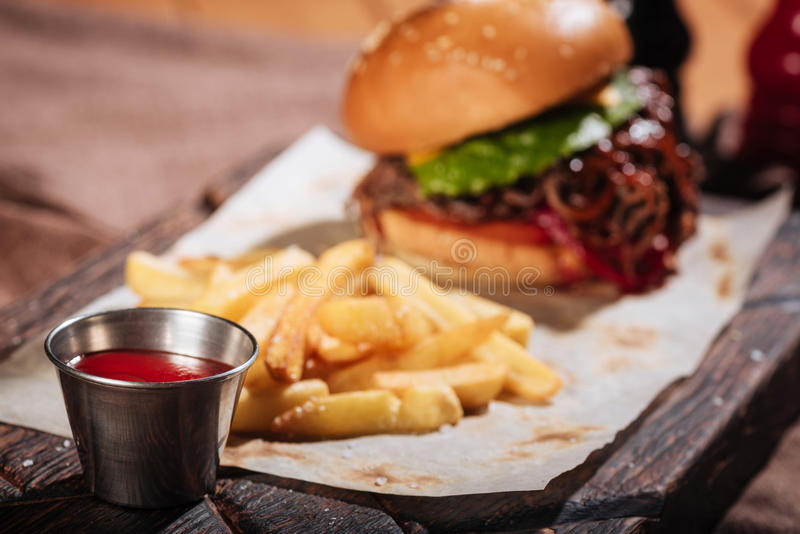 Sluit omhoog van saus die aan hamburger worden gediend stock fotografie