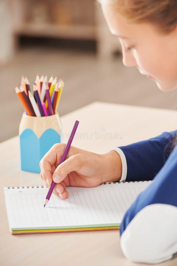 Sluit omhoog van schoolmeisje die in haar notitieboekje schrijven royalty-vrije stock afbeeldingen
