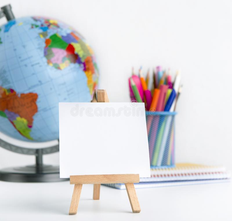 Sluit omhoog van schoolschildersezel, wereldbol en potloden op wit stock foto