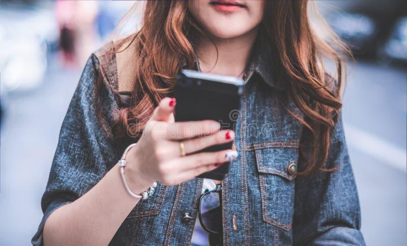 Sluit omhoog van Schoonheidsvrouw in jeansjasje gebruikend smartphone terwijl het lopen op straat Mensen en levensstijlenconcept  royalty-vrije stock foto