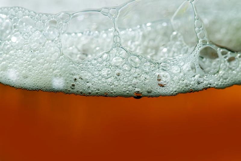 Sluit omhoog van schuimend bier in een glas royalty-vrije stock foto's