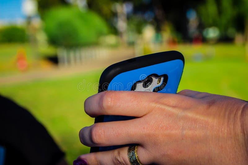 Sluit omhoog van smartphone van de vrouwenholding met haar hand stock afbeelding