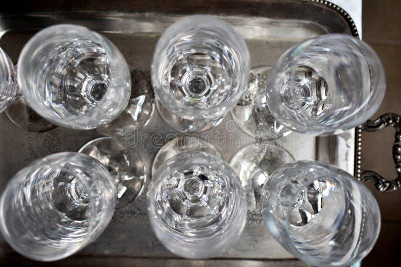sluit omhoog van sommige lege koppen van de glaswijn op zilveren dienblad zeer schone klaar om bij een restaurant in een partij w royalty-vrije stock afbeeldingen