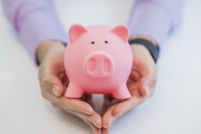 Sluit omhoog van spaarvarken in bedrijfs geïsoleerde mensenhanden op witte achtergrond stock afbeelding