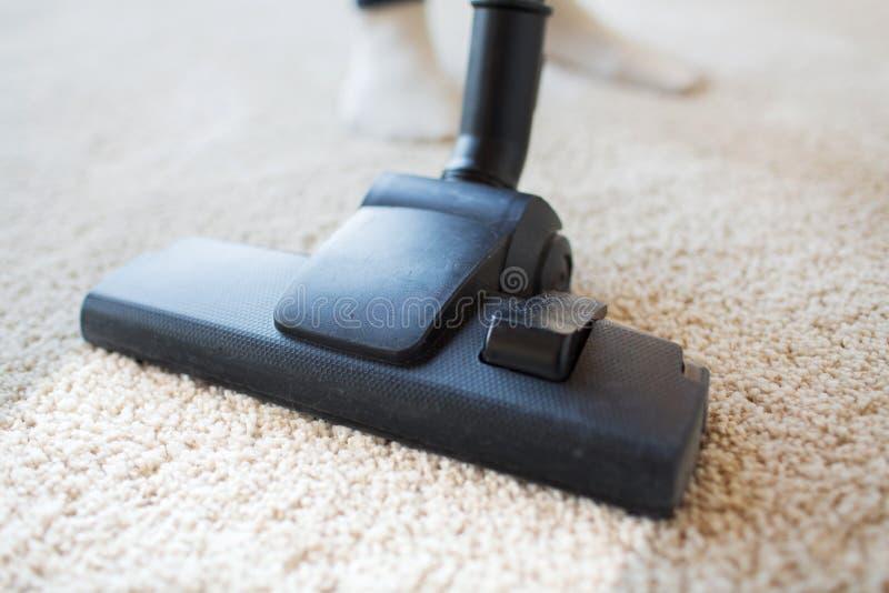 Sluit omhoog van stofzuiger schoonmakend tapijt thuis stock foto's