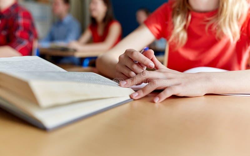 Sluit omhoog van student met boek het schrijven schooltest stock foto's