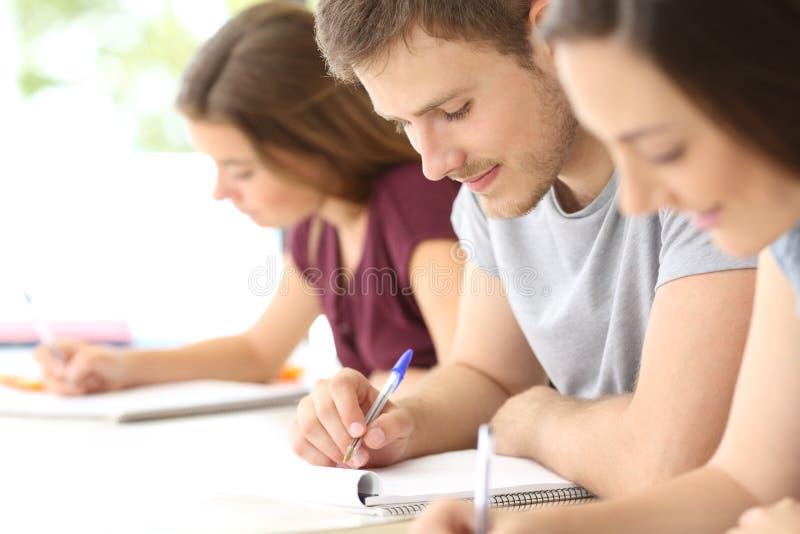 Sluit omhoog van studenten die nota's nemen bij klaslokaal royalty-vrije stock foto