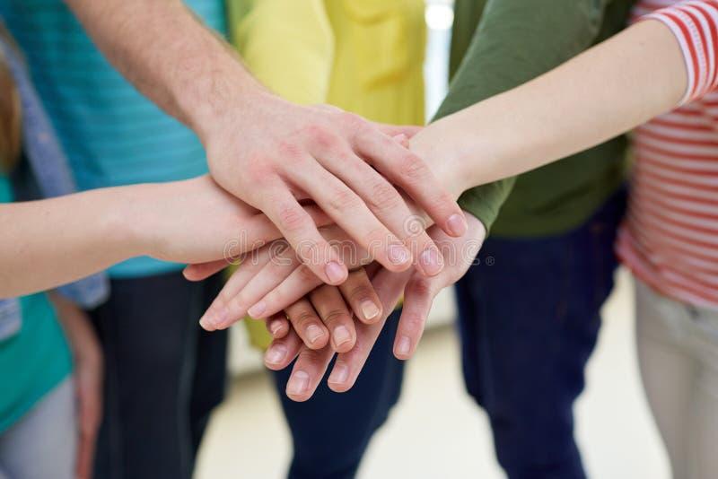Sluit omhoog van studenten of vrienden met handen op bovenkant stock foto's