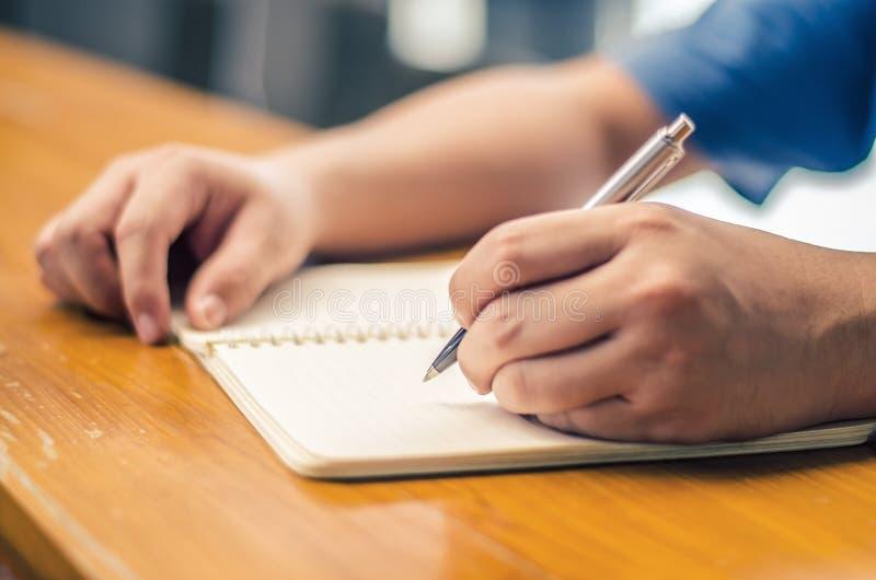 Sluit omhoog van studentenhand schrijvend op boek met pen royalty-vrije stock afbeeldingen