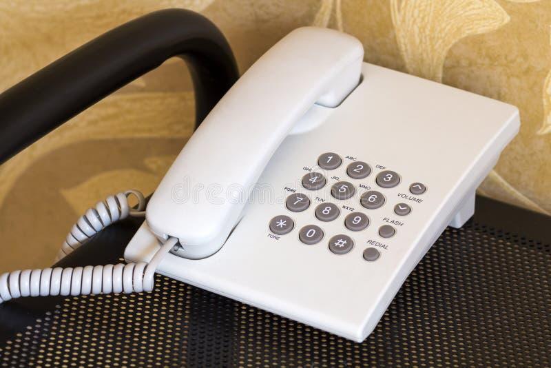 Sluit omhoog van telefoonapparaat bij bureau, mededeling techn stock afbeelding