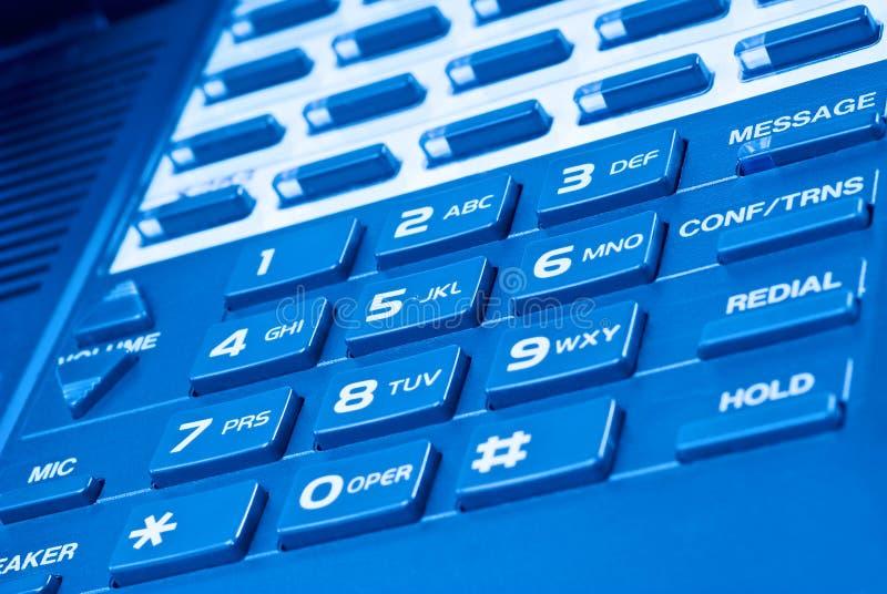 Sluit omhoog van telefoontoetsenbord met blauwe tint stock foto