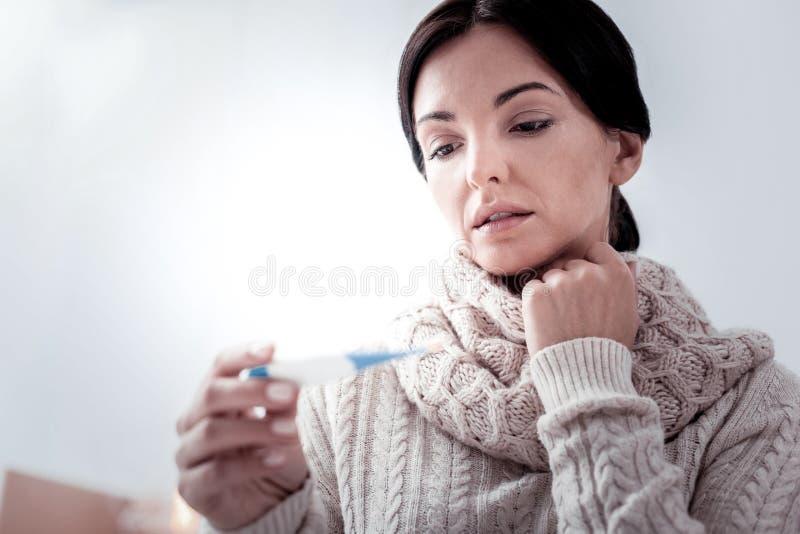 Sluit omhoog van teleurgestelde vrouw die thermometer bekijken royalty-vrije stock foto