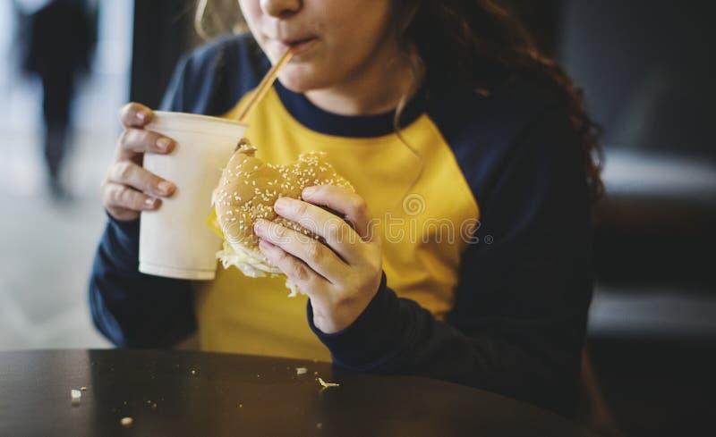 Sluit omhoog van tiener die het concept van de hamburgerzwaarlijvigheid eten stock foto's