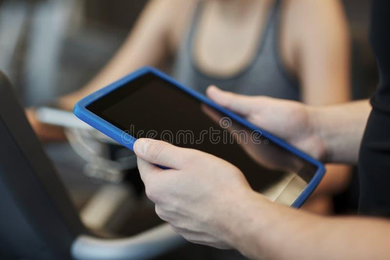 Sluit omhoog van trainerhanden met tabletpc in gymnastiek royalty-vrije stock fotografie
