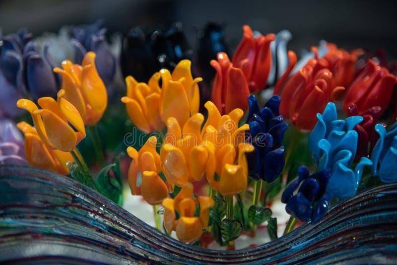 Sluit omhoog van tulpenbloemen in geel, rood en blauw in Murano-glas Artistieke totstandbrenging typisch van het Venetiaanse eila stock foto's