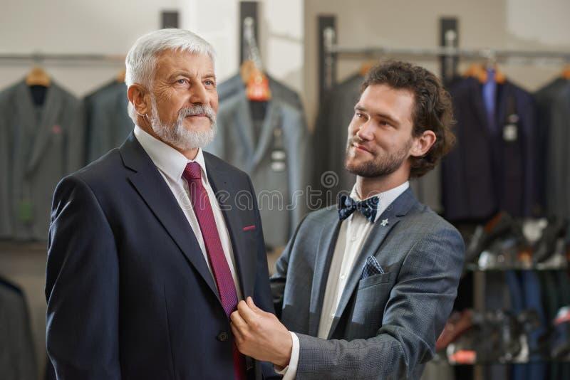 Sluit omhoog van twee elegante mensen die aan boutique bij het winkelen komen royalty-vrije stock foto
