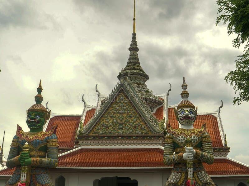 Sluit omhoog van twee gigantische demonstandbeelden bij wat arun tempel, Bangkok stock foto's