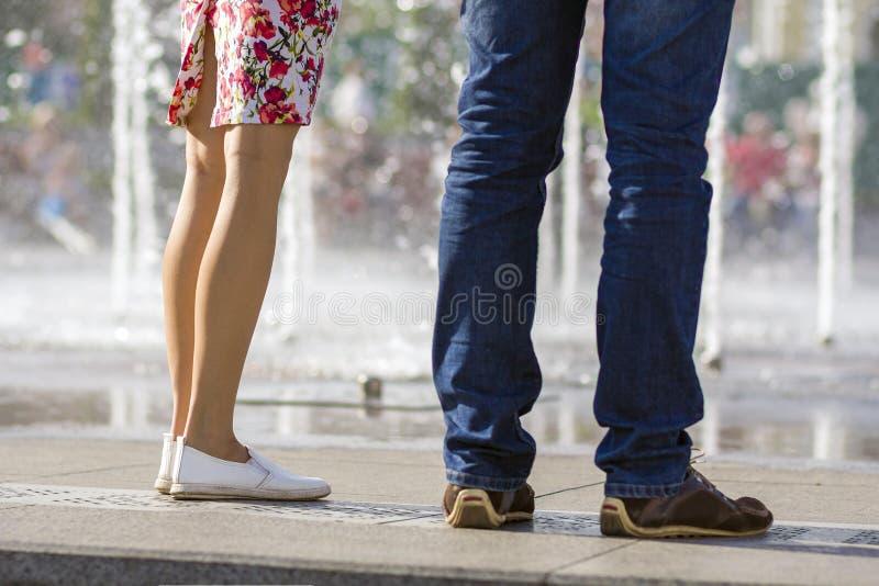 Sluit omhoog van twee paren benen, meisje in korte kleding met bloemenpatroon en witte schoenen en mens in jeans en bruine schoen royalty-vrije stock fotografie