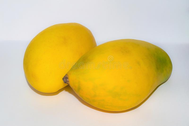 Sluit omhoog van twee verse rijpe mango's royalty-vrije stock foto