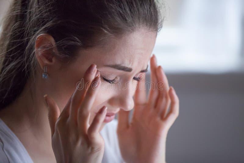 Sluit omhoog van uitgeput wijfje die aan hoofdpijn lijden royalty-vrije stock foto