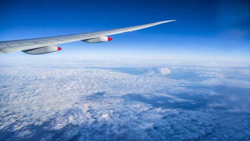 Sluit omhoog van venster met vliegtuigvleugel Mooie cloudscape met duidelijke blauwe hemel stock foto