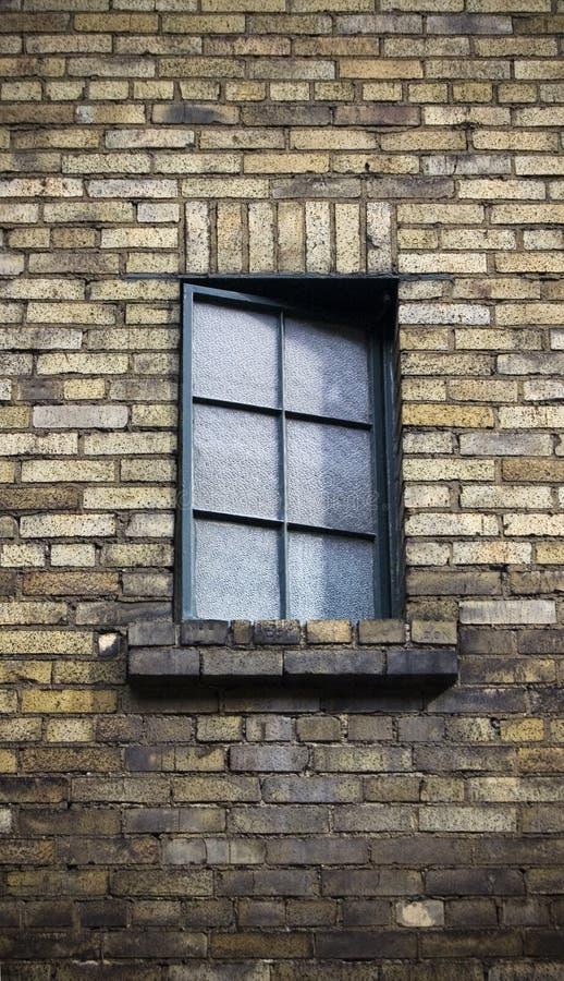 Sluit omhoog van venster op een doorstane bakstenen muur royalty-vrije stock afbeelding