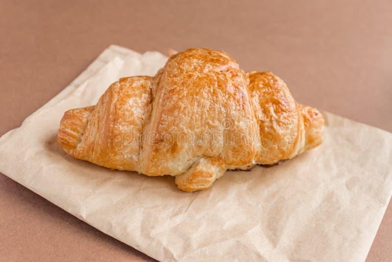 Sluit omhoog van vers gebakken Frans croissant op ambachtdocument voor ontbijt stock fotografie