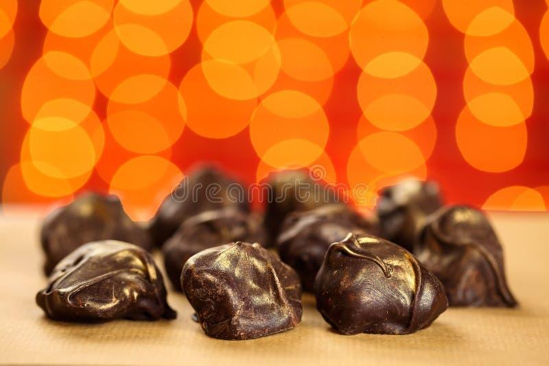 Sluit omhoog van vers, heerlijk en de gezonde eigengemaakte ruwe chocoladebonbons met gouden bestrooit tegen rode vage achtergron royalty-vrije stock afbeelding