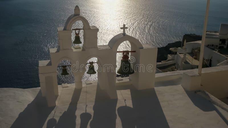 Sluit omhoog van vier kerkklokken bij zonsondergang in oia, santorini stock afbeeldingen