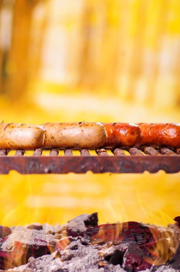 Sluit omhoog van vier roosterend worsten bij de barbecuegrill BBQ in de tuin Beierse worsten op een vage achtergrond stock afbeelding