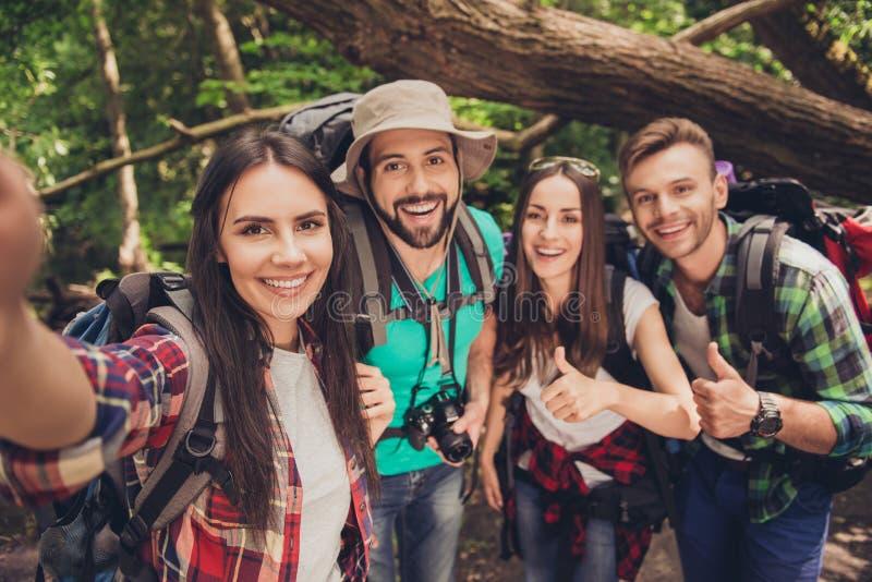 Sluit omhoog van vier vrolijke vrienden in het de zomer aardige hout, omhelzen, die voor een selfieschot stellen, dat de mooie do stock foto's
