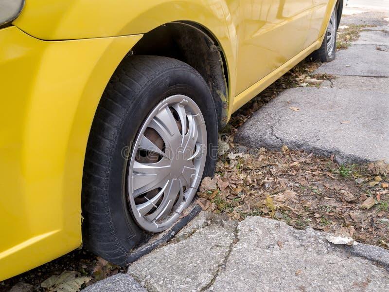 Sluit omhoog van vlakke of doordrongen banden van een gele auto of een taxi op een straat royalty-vrije stock afbeelding