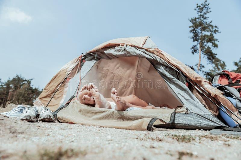 Sluit omhoog van voeten die backpackers rust na lange en uitputtende wandeling hebben royalty-vrije stock fotografie