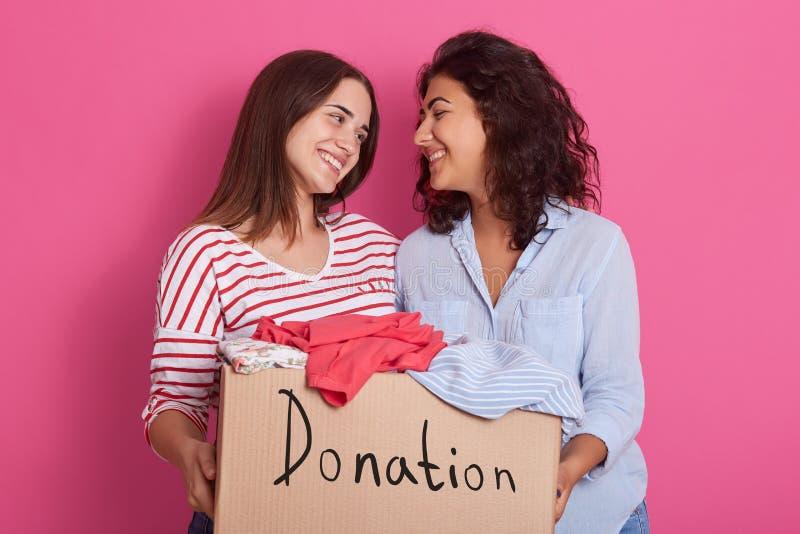 Sluit omhoog van vrolijke nuttige vrijwilligersmeisjes status geïsoleerd over roze achtergrond, die doos met verschillende kleren stock fotografie