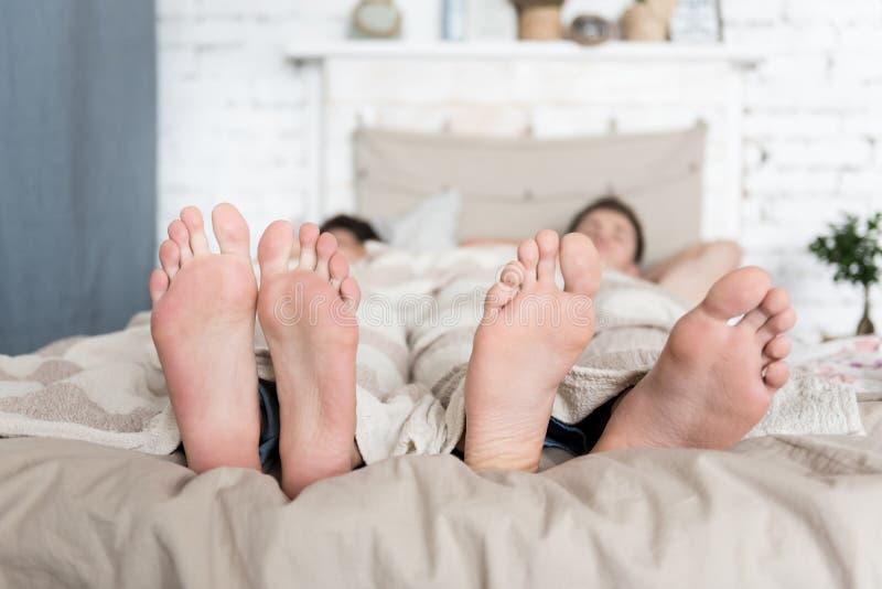 Sluit omhoog van vrolijke parenvoeten liggend in bed stock afbeelding