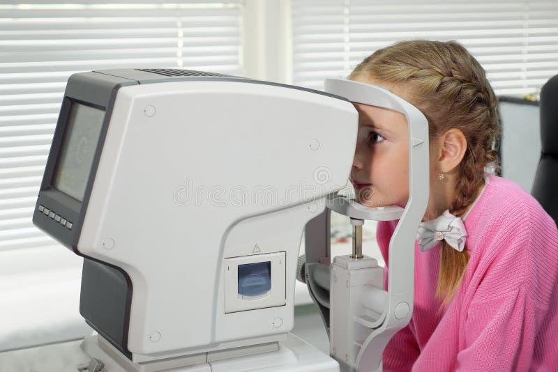 Sluit omhoog van vrouw arts het werken met de refractometermachine Een klein meisje die haar geteste ogen hebben royalty-vrije stock afbeelding