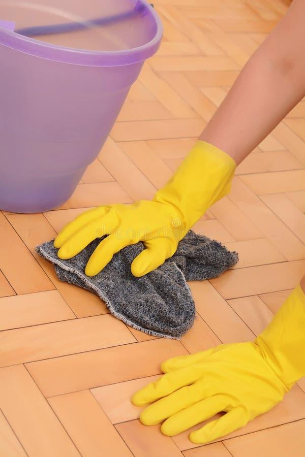 Sluit omhoog van vrouw die de vloer met doek schoonmaken stock fotografie