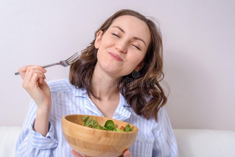 Sluit omhoog van vrouw die gezonde plantaardige salade met genoegen eten stock foto