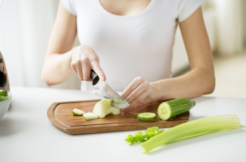 Sluit omhoog van vrouw die groene groenten hakken royalty-vrije stock afbeelding